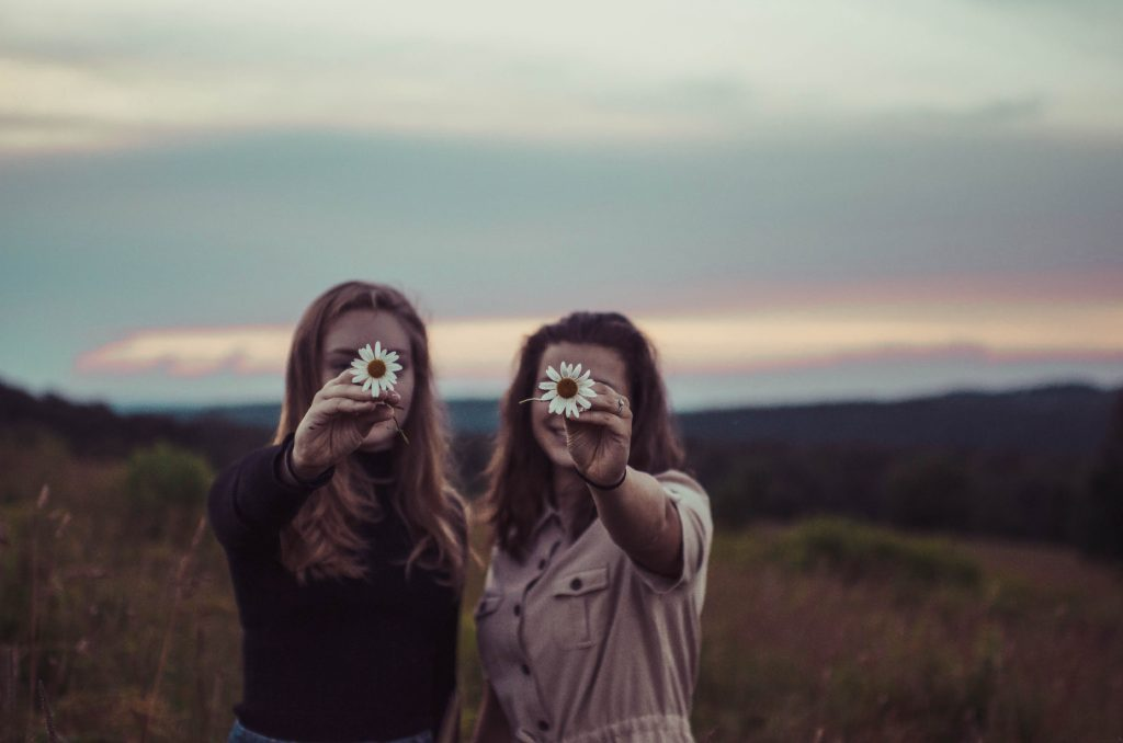 Funny friendship day quotes for you to enjoy with your bffs-two girls holding flower.